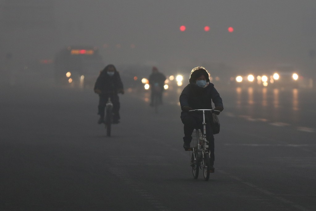 BEIJING, CHINA - JANUARY 29: Beijing residents wearing the mask ride amid fog during severe pollution on January 29, 2013 in Beijing, China. The 4th dense fog envelops Beijing with pollution at hazardous levels in January. (Photo by Feng Li/Getty Images)